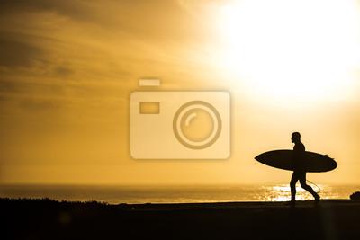 Surfista en una hermosa puesta de sol de oro en Santa Cruz