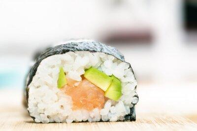 Póster Sushi con salmón, aguacate, arroz en algas y palillos en la mesa de madera