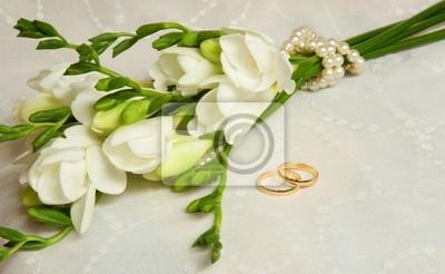 Tarjeta de boda. Dos anillos de oro con velo y las flores nupciales
