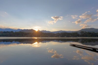 The sun set behind the mountain and reflect on the water
