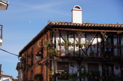Póster Típica casa de ladrillo con estructura visible de madera, techo de teja árabe, chimeneas de ladrillo, tiestos y flores, galerías de madera, faroles típicos españoles, platos y azulejos de cerámica, pe