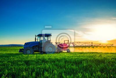 Tractor agrícola arando y rociando en el campo