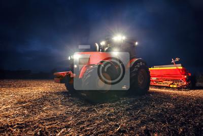 Tractor que prepara la tierra con el cultivador de semillero en la noche
