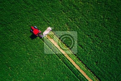 Tractor que siega el campo verde, vista aérea