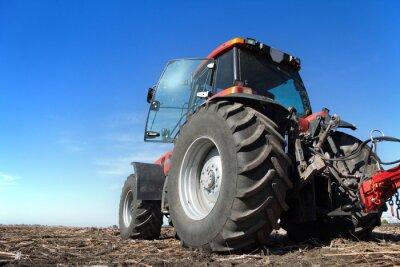 Póster Tractor trabajando en el campo día soleado