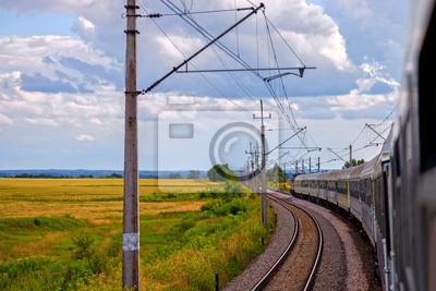 Tren de pasajeros en el ferrocarril en día de verano.