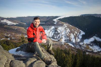 Turismo sentado en la roca grande en la cima de la montaña