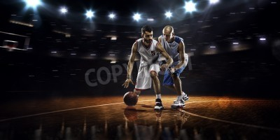 Póster Two basketball players in action in gym in lights