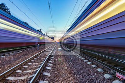 Two trains move fast to the different directions at sunset time.