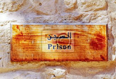 Un antiguo letrero de madera que cuelga de prisión en una pared.