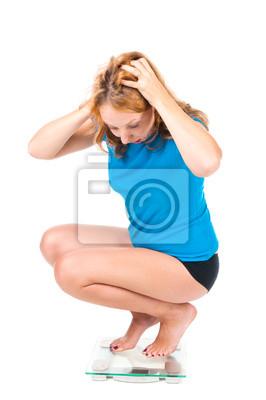Una chica joven que grita mientras que ella ve su peso en la escala de