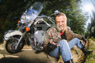 Unshaven motociclista masculino en chaqueta de cuero y blue jeans sentado en carretera cerca de motocicleta y dando el cuerno de diablo gesto y sonriendo. Imagen horizontal. Efecto de desenfoque de la