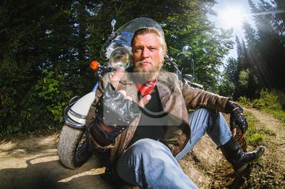 Unshaven motociclista masculino en chaqueta de cuero y blue jeans sentado en el camino de tierra cerca de la motocicleta y dando el gesto de cuernos de diablo. Imagen horizontal