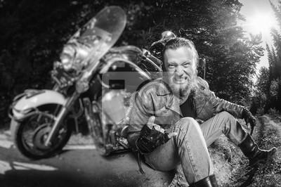 Unshaven motociclista masculino en chaqueta de cuero y pantalones vaqueros sentado en la carretera cerca de la motocicleta y dando el gesto de los cuernos del diablo y sonriendo. Imagen horizontal. Ef