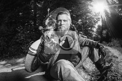 Unshaven motociclista masculino en chaqueta de cuero y pantalones vaqueros sentados en camino de tierra cerca de la motocicleta y dando el gesto de cuernos de diablo. Imagen horizontal. en blanco y ne