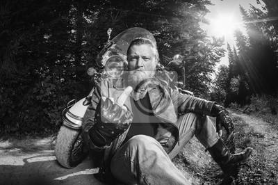 Unshaven motociclista masculino en chaqueta de cuero y pantalones vaqueros sentados en camino de tierra cerca de motocicleta y mostrando el dedo medio. Imagen horizontal. en blanco y negro