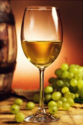 Póster Vaso de vino blanco delante de uvas verdes y viejo barril
