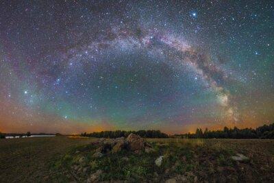 Póster Vía Láctea brillante bajo las rocas