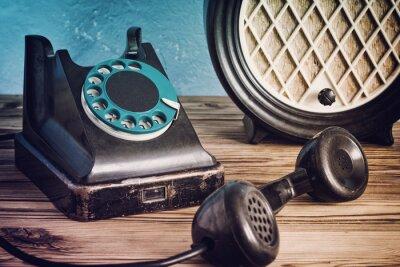 Póster Vintage teléfono y radio en una mesa de madera