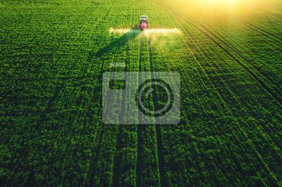 Vista aérea del tractor agrícola que ara y que pulveriza en campo