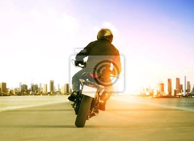 Vista trasera de hombre montando motocicleta en carretera de tráfico urbano para el ocio de personas