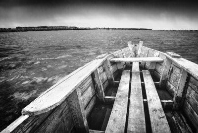 Wooden boat on a river. Black and white