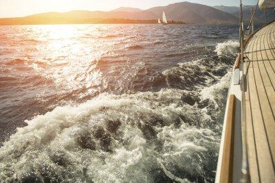 Póster Yate, mar por la borda, navegando regata durante la puesta del sol.