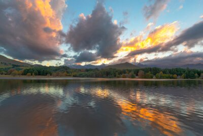 Yellow colored clouds at sunset reflection on water