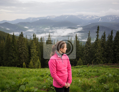 young girl in the mountains looking around in the Carpathian mountains after rain