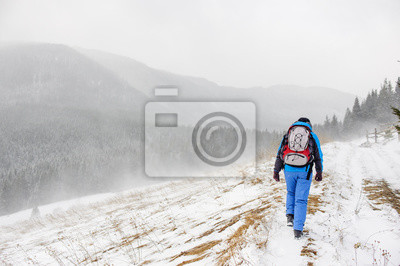 Young girl traveling in winter mountains