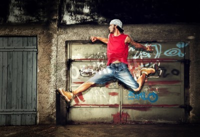 Póster Young man jumping / dancing on grunge graffiti wall background
