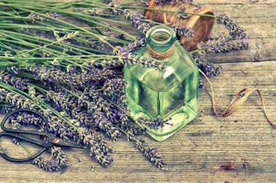 Vinilo Aceite de hierbas de lavanda con flores frescas sobre fondo de madera
