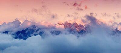 Vinilo Alta gama de montañas en las nubes durante la salida del sol. Hermoso paisaje panorámico