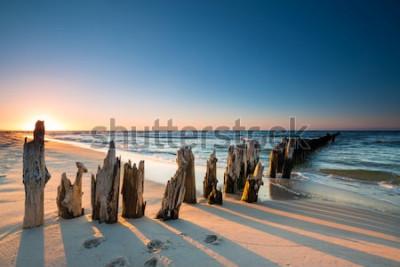 Vinilo Atardecer en la playa del mar Báltico y antiguo dique de madera.