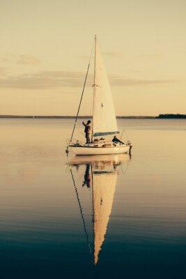 Vinilo Barco de vela en un lago tranquilo con la reflexión en el agua. Paisaje escénico sereno.