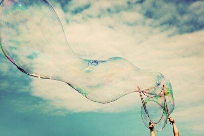 Vinilo Blowing grandes pompas de jabón en el aire. La libertad de la vendimia, los conceptos de verano.
