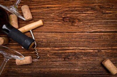 Vinilo Botella de vino, sacacorchos y corchos en mesa de madera. Fondo