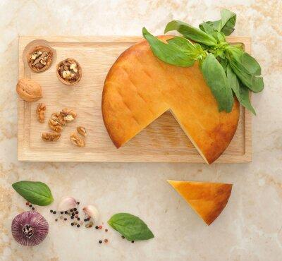 Vinilo Cabeza de queso Suluguni ahumado en tablero de madera con nueces y