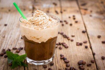 Vinilo Café de hielo con la crema batida en un vaso sobre la mesa de madera