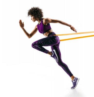 Vinilo Chica fuerte en silueta usando una banda de resistencia. La foto de la muchacha africana joven realiza ejercicios de la aptitud aislados en el fondo blanco. Vista lateral