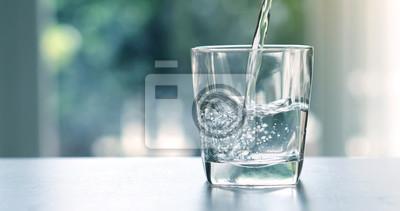 Vinilo Cierre el agua purificada bebida fresca que vierte de la botella en la mesa en la sala de estar
