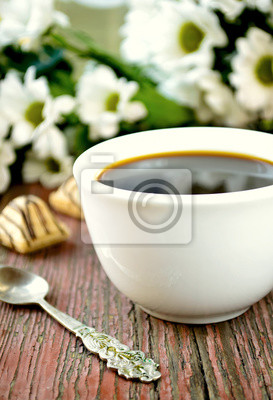 Coffee with flowers on wooden table