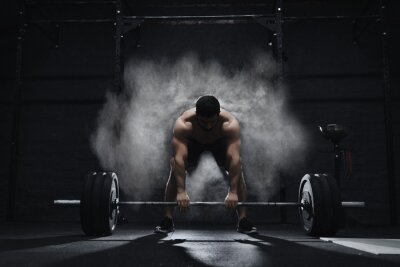 Vinilo Crossfit athlete preparing to lift heavy barbell in a cloud of dust at the gym. Barbell magnesia protection.