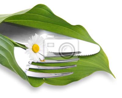 Vinilo Cuchillo y tenedor en la hoja verde con manzanilla sobre fondo blanco