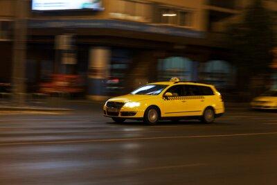 Vinilo de taxi amarillo se mueve en la calle la noche de la ciudad