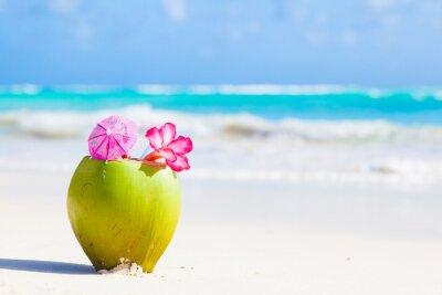 Vinilo dos fresco cóctel de coco en la playa tropical con flores