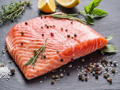 Vinilo El salmón fresco en la tabla de cortar negro.