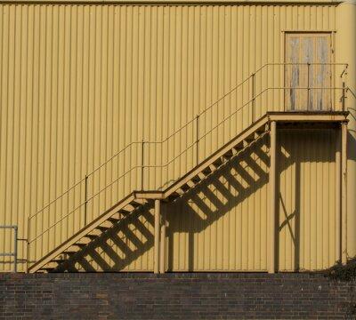 Vinilo Escaleras que conducen a través de una pared de metal sidinf.