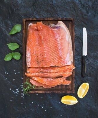 Vinilo Filete de salmón ahumado con limón, hierbas frescas y criado en tabla de servir de madera sobre fondo de piedra oscura