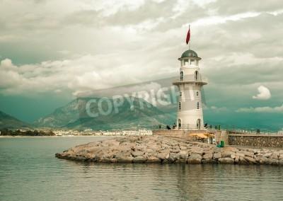 Vinilo Hermoso paisaje de la naturaleza con rango de montañas, el cielo nublado y el faro en el puerto de Alanya, Turquía